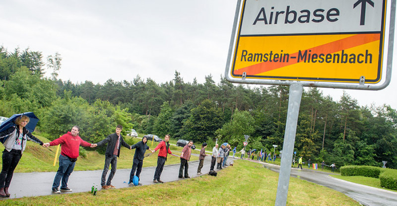 """Activists attend a rally """"Stop-Ramstein"""" on the road leading to US Air Force Base in Ramstein-Miesenbach on June 11, 2016. © Oliver Dietze / DPA / AFP"""