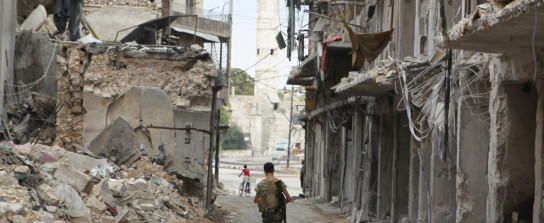 A Free Syrian Army fighter carries his weapon as he walks past damaged buildings in the old city of Aleppo, Syria August 30, 2015. REUTERS/Abdalrhman Ismail - RTX241FW