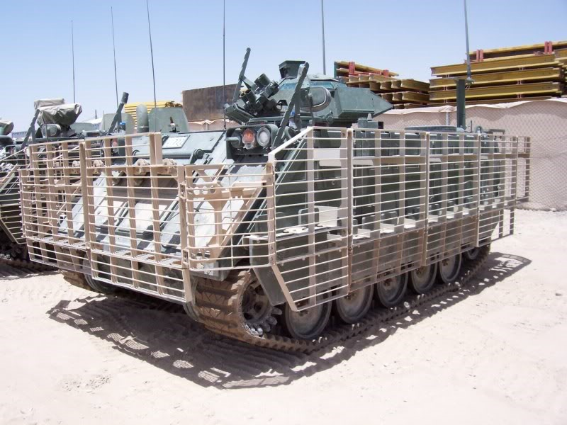M113A3 fitted with slat armor to protect against shaped-charge munitions in urban environments. The armor serves the double purpose of allowing for added external stowage of gear.