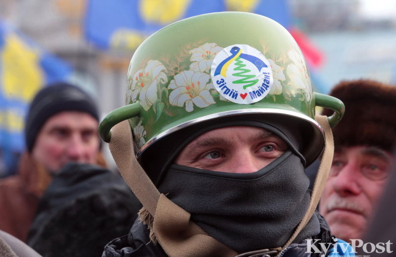 """An anti-government protester wears a pot as a helmet at a rally on Maidan Nezalezhnosti on Jan. 19, 2014. On Jan. 16 the Verkhovna Rada, Ukraine's parliament, passed a controversial raft of legislation (dubbed the """"Dictatorship Laws"""" based on similar Russian laws that criminalized a range of protest actions, including the wearing of helmets by protesters. EuroMaidan supporters responded by donning colanders, pots, and metal buckets in mockery of the parliament, which in any case had passed the repressive laws illegally by a show of hands."""
