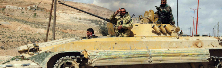 A Syrian army soldier flashes a 'V for victory' sign as his tank travels northeast of Damascus Getty Images