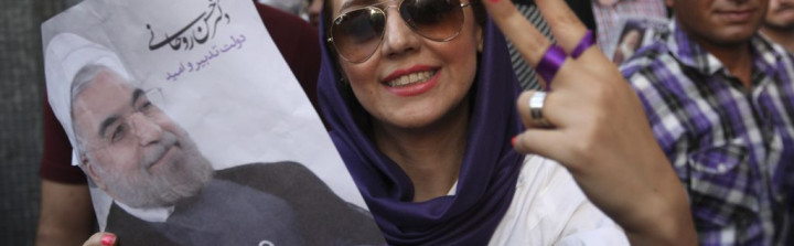 A female supporter of Iranian presidential candidate Hasan Rowhani flashes a victory sign as she holds his poster during a celebration gathering in Tehran, Iran, Saturday, June 15, 2013 (photo credit: AP/Vahid Salemi)