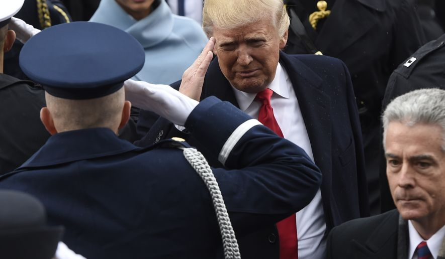 President Donald Trump salutes military personnel as he leaves Capitol Hill in Washington, Friday, Jan. 20, 2017, after taking the presidential oath. (Saul Loeb/Pool Photo via AP)