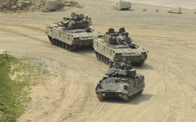 Two K21 IFVs follow an M3A2 Bradley at a military base in South Korea. Note the size comparison of the different vehicles.