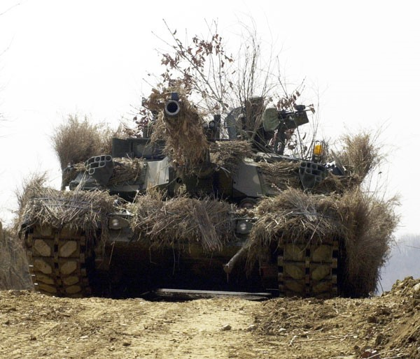 A heavily camouflaged K1A1/A2/E2 MBT during maneuvers close to the DMZ.