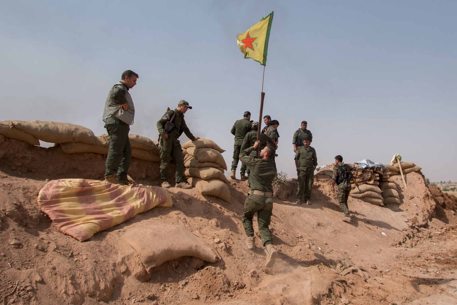 A YPG fighter raises a YPG flag over a barrier in Tel al-Aghbish village, which they retook control of from IS. Source: Reuters