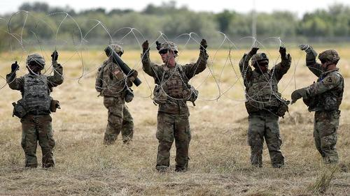 US Troops Lay Down Razor Wire At Southern Border